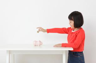 貯金箱にお金を入れるおかっぱの女の子の写真素材 [FYI02031420]