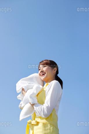 青空の下でまっ白なタオルを持つ女性の写真素材 [FYI02031460]