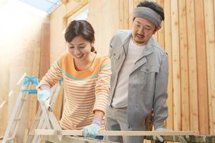 大工さんに作業を習う女性の写真素材 [FYI02031465]