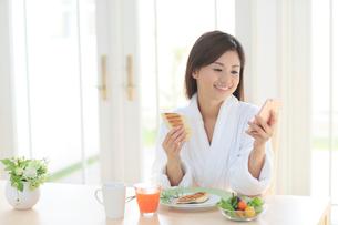 朝食を食べながらスマートフォンを持つバスローブ姿の女性の写真素材 [FYI02031483]