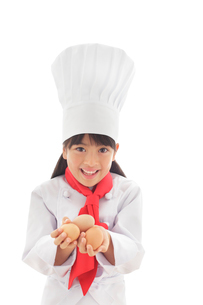 卵を持つシェフの女の子の写真素材 [FYI02031527]
