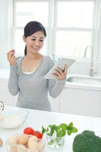 キッチンでタブレットPCを見てメニューを検索する女性の写真素材 [FYI02031540]