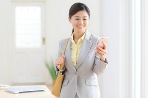 携帯を操作しながら出勤する女性の写真素材 [FYI02031542]