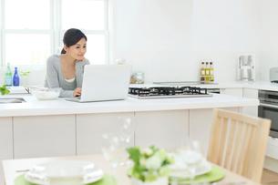 キッチンでパソコンを見てメニューを検索する女性の写真素材 [FYI02031575]