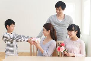 母の日のプレゼントを贈る子どもたちと見守るお父さんの写真素材 [FYI02031608]