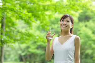 新緑の中で水を飲む若い女性の写真素材 [FYI02031633]