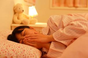 ベッドで咳をする体調不良の女の子の写真素材 [FYI02031649]