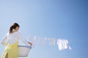 青空の下で家族の洗濯物を取り込む女性の写真素材 [FYI02031661]