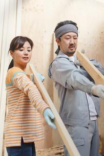 大工さんに作業を習う女性の写真素材 [FYI02031704]