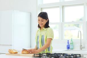明るいキッチンで料理をする女性の写真素材 [FYI02031707]