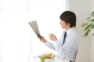 朝食を食べながら新聞を読むビジネスマンの写真素材 [FYI02031725]