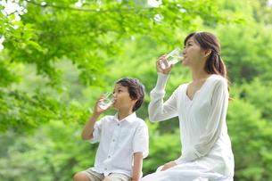 新緑の中で水を飲むお母さんと男の子の写真素材 [FYI02031735]
