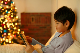 クリスマスツリーのある寝室で本を読む男の子の写真素材 [FYI02031819]