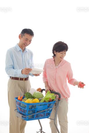 ショッピングカートを押しながら買い物をするシニアの夫婦の写真素材 [FYI02031943]