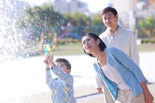 水鉄砲で遊ぶ少年と両親の写真素材 [FYI02032177]