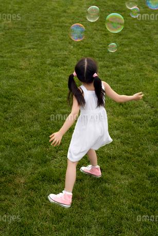 シャボン玉を追いかける少女の写真素材 [FYI02032251]