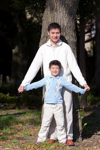 木の前に立つ父親と少年の写真素材 [FYI02032361]