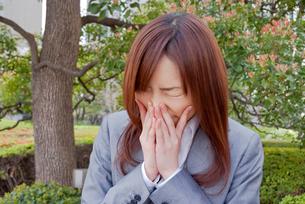 くしゃみをする若い女性の写真素材 [FYI02032465]