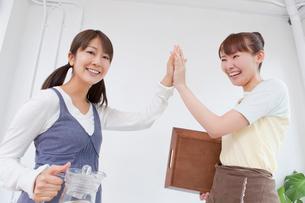 ハイタッチをするアルバイトの女性2人の写真素材 [FYI02032525]