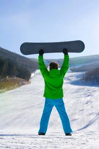 スノーボードを持ち上げる若い男性の写真素材 [FYI02032753]