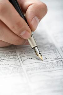 株価をチェックする男性の手の写真素材 [FYI02032790]