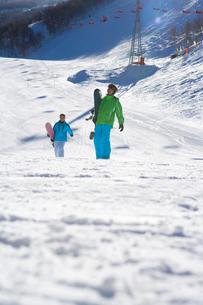 スノーボードを持って歩く若いカップルの写真素材 [FYI02032886]