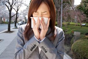 鼻をかむ若い女性の写真素材 [FYI02032893]