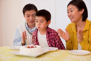 バースデーケーキのロウソクを消す少年の写真素材 [FYI02032951]