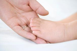 赤ちゃんの足を触る父親の手の写真素材 [FYI02033298]