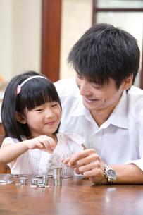 硬貨を数える娘と父親の写真素材 [FYI02033581]