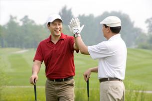 ゴルフでハイタッチをする2人の男性の写真素材 [FYI02033588]