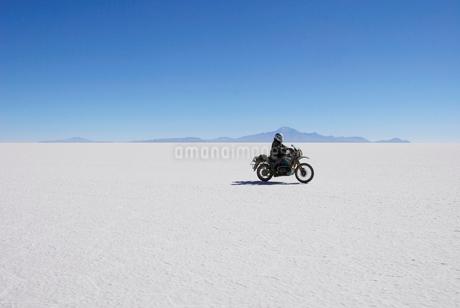 ウユニ塩田を進むバイクの写真素材 [FYI02034542]