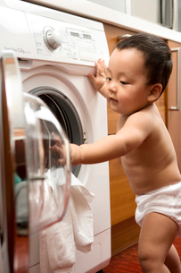 洗濯機に服を入れる赤ちゃんの写真素材 [FYI02034546]
