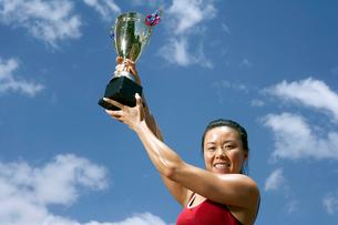 トロフィーを手にした女性陸上選手の写真素材 [FYI02034613]