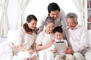 タブレットPCを見る家族の写真素材 [FYI02034868]