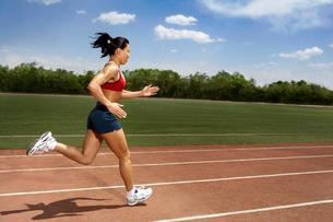 トラックを走る女性陸上選手の写真素材 [FYI02034882]