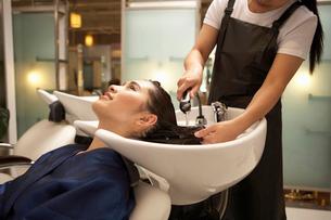 洗髪をしてもらう若い女性と美容師の写真素材 [FYI02035021]