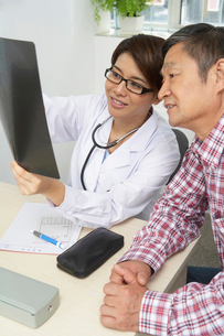 レントゲン写真を見る女性医師と患者の写真素材 [FYI02035318]