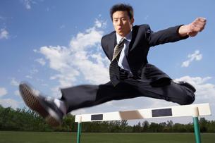 ハードルを飛び越えるビジネスマンの写真素材 [FYI02035322]