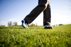 スイング後に飛び散る芝生と男性の足の写真素材 [FYI02035336]