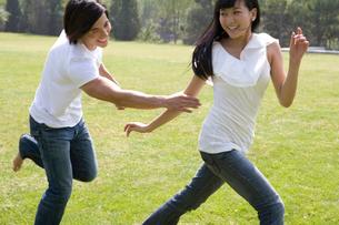 追いかけっこをする若いカップルの写真素材 [FYI02035370]
