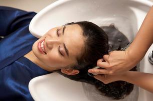 洗髪をしてもらう若い女性の写真素材 [FYI02035446]