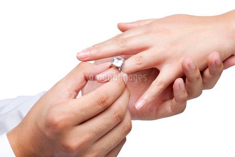 女性の指に婚約指輪をはめる男性の手の写真素材 [FYI02035998]