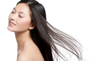 長髪の黒髪を風になびかせる若い女性の写真素材 [FYI02036051]