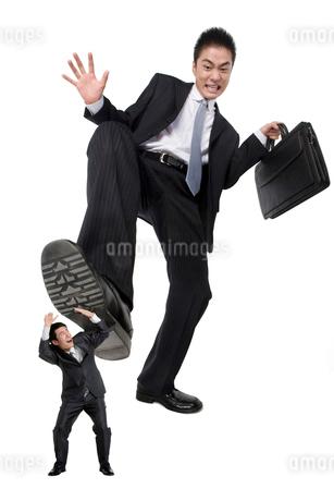 小さなビジネスマンを踏みつけようとする男性の写真素材 [FYI02036265]