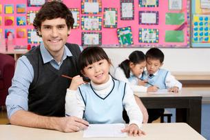 白人の先生と授業を受ける小学生の写真素材 [FYI02036482]