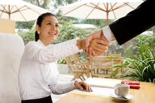 ビジネスマンと握手をする若い女性の写真素材 [FYI02036538]