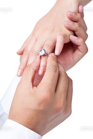 女性の指に婚約指輪をはめる男性の手の写真素材 [FYI02036559]