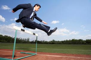 ハードルを飛び越えるビジネスマンの写真素材 [FYI02036789]