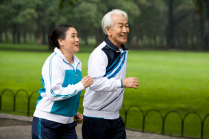 公園を走るシニアカップルの写真素材 [FYI02037125]
